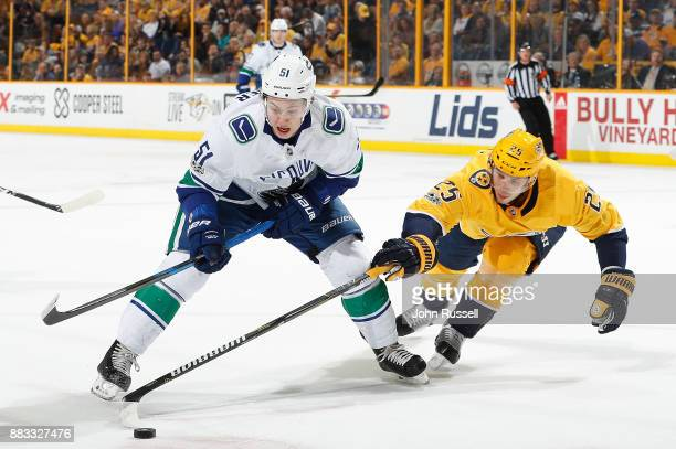 Alexei Emelin of the Nashville Predators defends against Troy Stecher of the Vancouver Canucks during an NHL game at Bridgestone Arena on November 30...