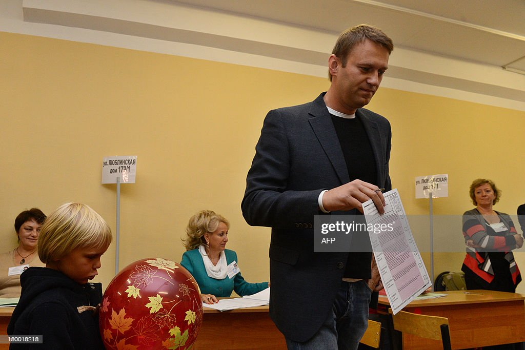 Alexei Navalny, a top critic of President Vladimir Putin, goes to cast his ballot at a polling station during a mayoral election in Moscow, on September 8, 2013, with Navalny's son Zakhar (L) attending. Navalny faced today a Kremlin-backed incumbent in a hotly contested Moscow mayoral poll, the first time an opposition leader has been allowed to stand in a high-profile election.