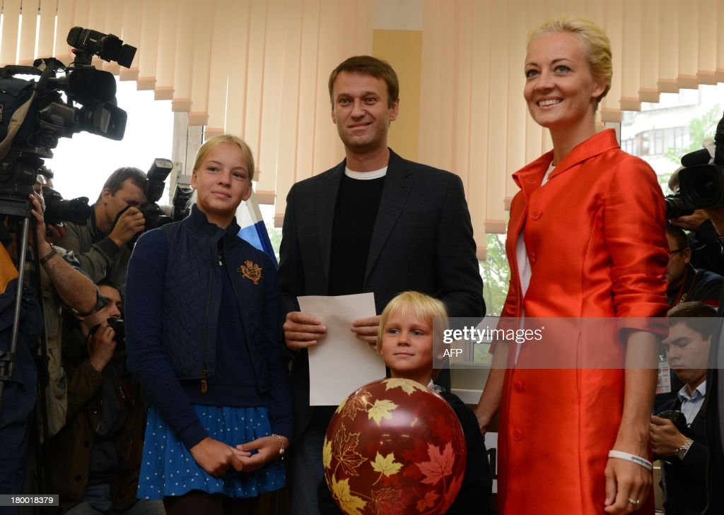 Alexei Navalny, a top critic of President Vladimir Putin, holds his ballot at a polling station during a mayoral election in Moscow, on September 8, 2013, with Navalny's family, daughter Dasha (R), son Zakhar (L) and wife, Yulia (R), attending. Navalny faced today a Kremlin-backed incumbent in a hotly contested Moscow mayoral poll, the first time an opposition leader has been allowed to stand in a high-profile election.