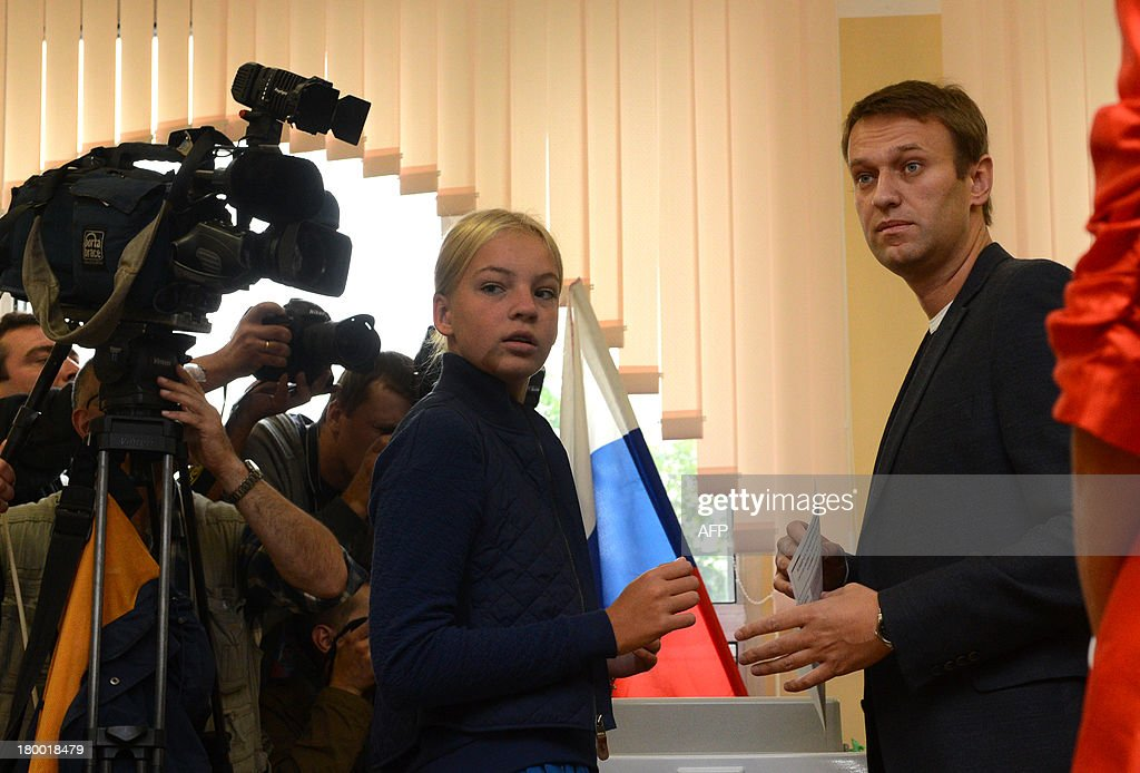 Alexei Navalny (R), a top critic of President Vladimir Putin, prepares to cast his ballot at a polling station during a mayoral election in Moscow, on September 8, 2013, with his daughter, Dasha (L), attending. Navalny faced today a Kremlin-backed incumbent in a hotly contested Moscow mayoral poll, the first time an opposition leader has been allowed to stand in a high-profile election.