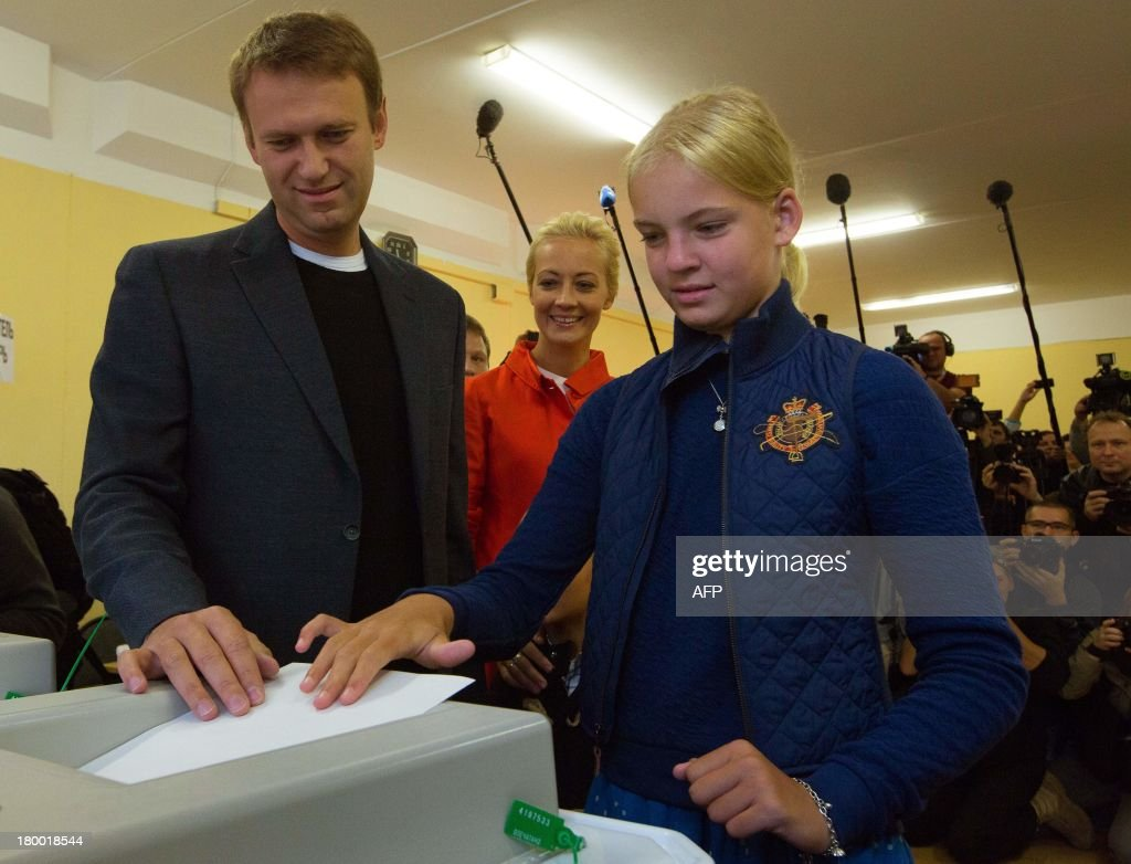 Alexei Navalny (L) and his daughter, Dasha (R), cast Navalny's ballot at a polling station during a mayoral election in Moscow, on September 8, 2013. Navalny, a top critic of President Vladimir Putin, faced today a Kremlin-backed incumbent in a hotly contested Moscow mayoral poll, the first time an opposition leader has been allowed to stand in a high-profile election.