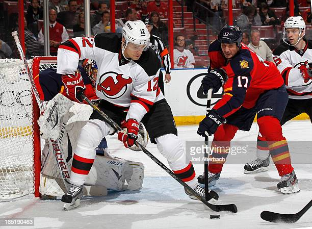 Alexei Ponikarovsky of the New Jersey Devils attempts to gain control of the puck while being defended by Filip Kuba of the Florida Panthers at the...