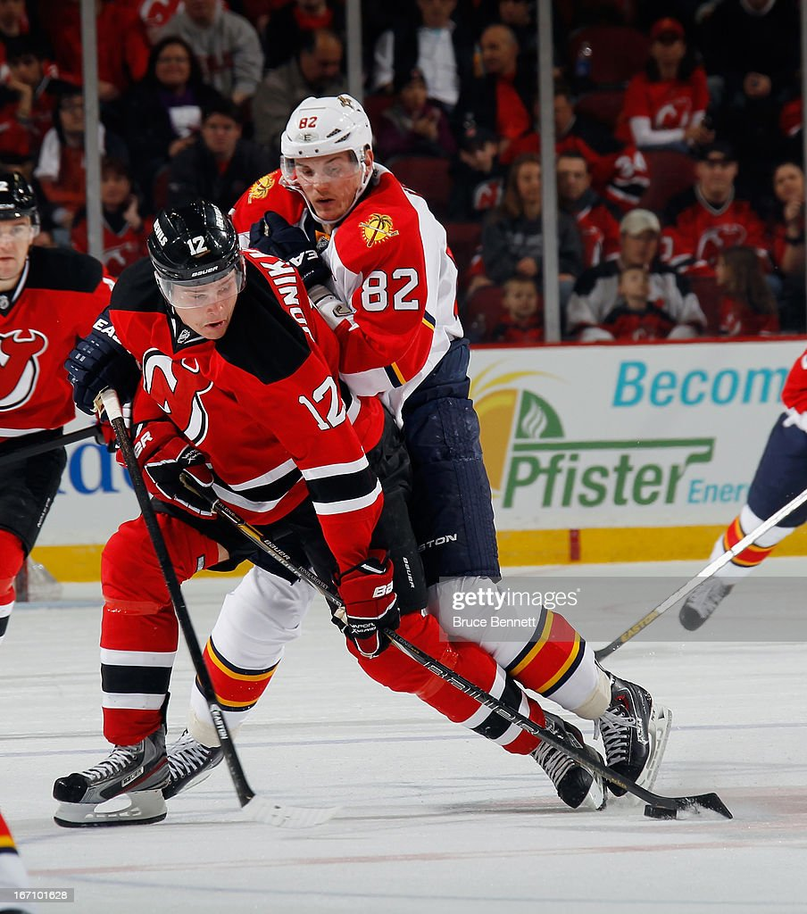 Alexei Ponikarovsky #12 of the New Jersey Devils controls the puck while being checked by Tomas Kopecky #82 of the Florida Panthers at the Prudential Center on April 20, 2013 in Newark, New Jersey.