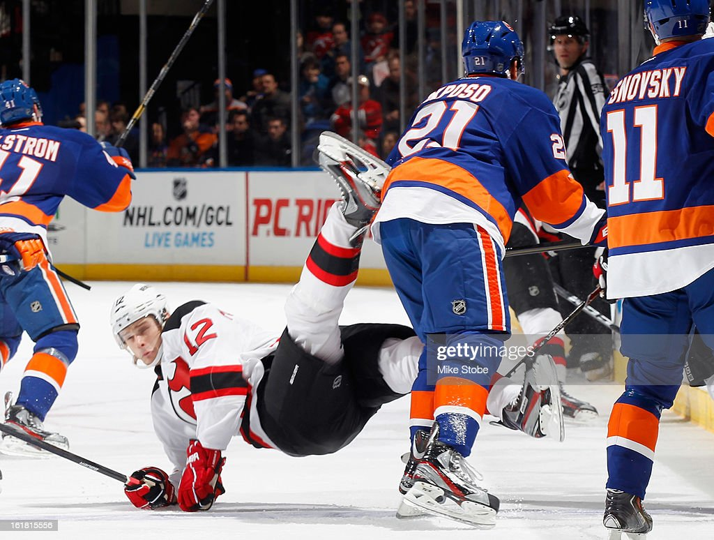 Alexei Ponikarovsky #12 of the New Jersey Devils falls to the ice in front of Kyle Okposo #21 of the New York Islanders at Nassau Veterans Memorial Coliseum on February 16, 2013 in Uniondale, New York.