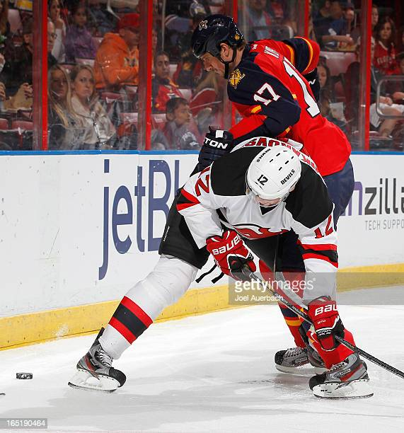 Alexei Ponikarovsky of the New Jersey Devils is checked off the puck by Filip Kuba of the Florida Panthers at the BBT Center on March 30 2013 in...