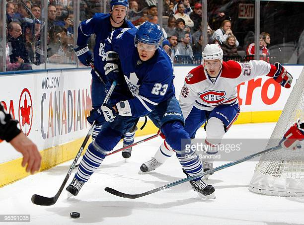 Alexei Ponikarovsky of the Toronto Maple Leafs carries the puck as teammate Wayne Primeau and Josh Gorges of the Montreal Canadiens look on during...