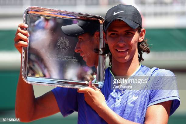 Alexei Popyrin of Australia celebrates victory with the trophy following the boys singles final match against Nicola Kuhn of Spain on day fourteen of...