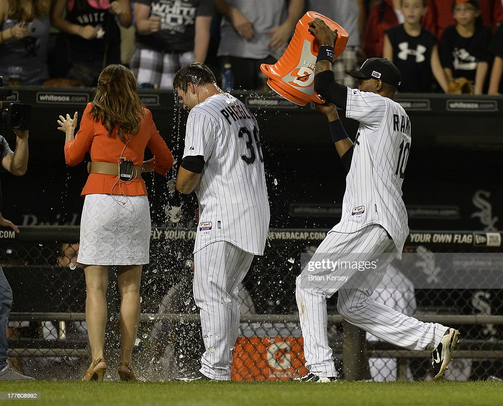<a gi-track='captionPersonalityLinkClicked' href=/galleries/search?phrase=Alexei+Ramirez&family=editorial&specificpeople=690568 ng-click='$event.stopPropagation()'>Alexei Ramirez</a> #10 of the Chicago White Sox (R) douses teammate Josh Phegley #36 with ice water as he is interviewed by a television reporter after hitting a game-winning, RBI single scoring Avisail Garcia #26 during the ninth inning of the 2013 Civil Rights Game against the Texas Rangers at U.S. Cellular Field on August 24, 2013 in Chicago, Illinois. The White Sox won 3-2.