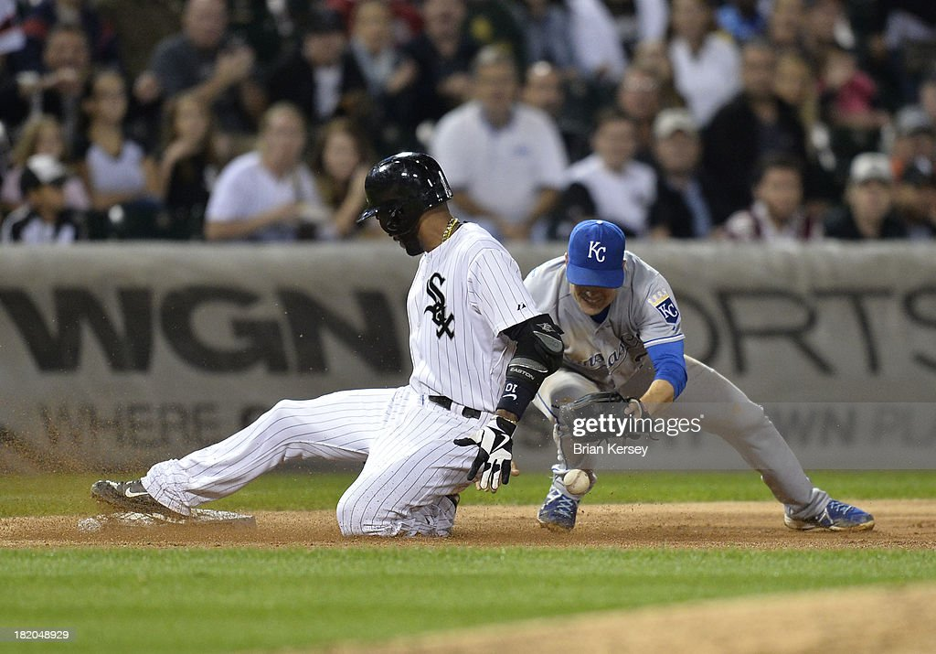 Alexei Ramirez #10 of the Chicago White Sox slides safely into third base with a triple as third baseman Jamey Carroll #21 of the Kansas City Royals loses the ball while trying to tag him out during the fourth inning at U.S. Cellular Field on September 27, 2013 in Chicago, Illinois.