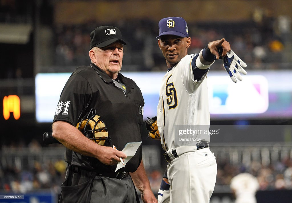 Alexei Ramirez #10 of the San Diego Padres points out a vocal San Francisco Giants fan to umpire Bob Davidson during the eighth inning of a baseball game at PETCO Park on May 18, 2016 in San Diego, California.