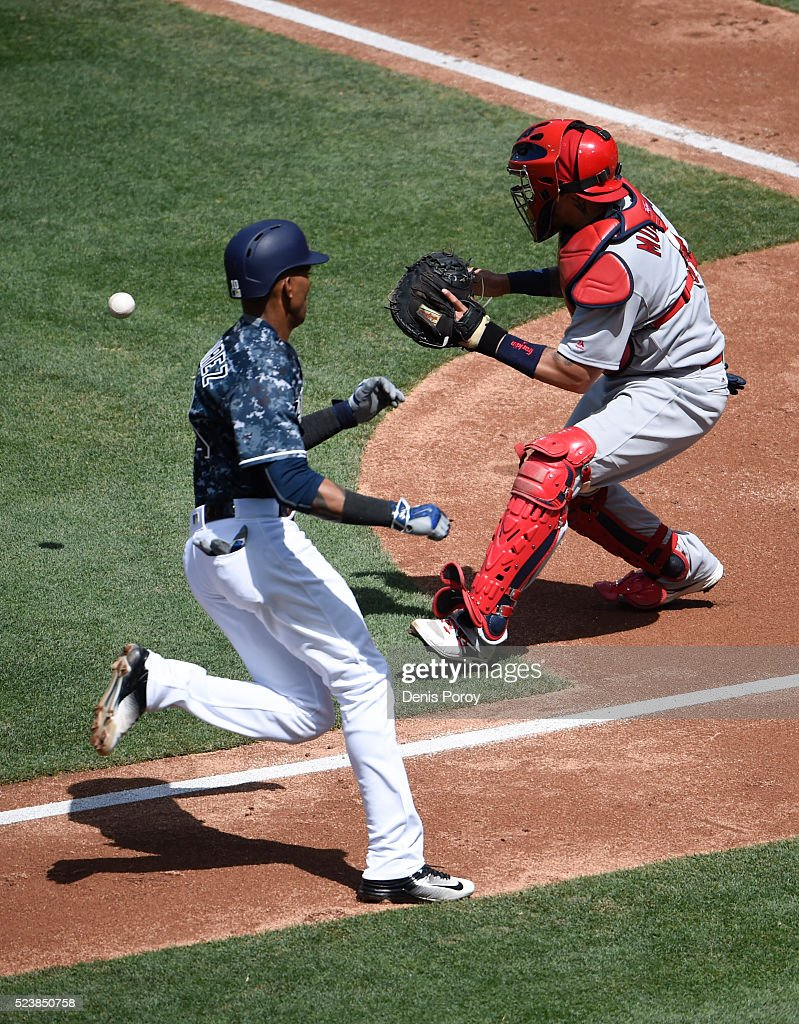Alexei Ramirez #10 of the San Diego Padres scores ahead of the throw to Yadier Molina #4 of the St. Louis Cardinals during the second inning of a baseball game at PETCO Park on April 24, 2016 in San Diego, California.