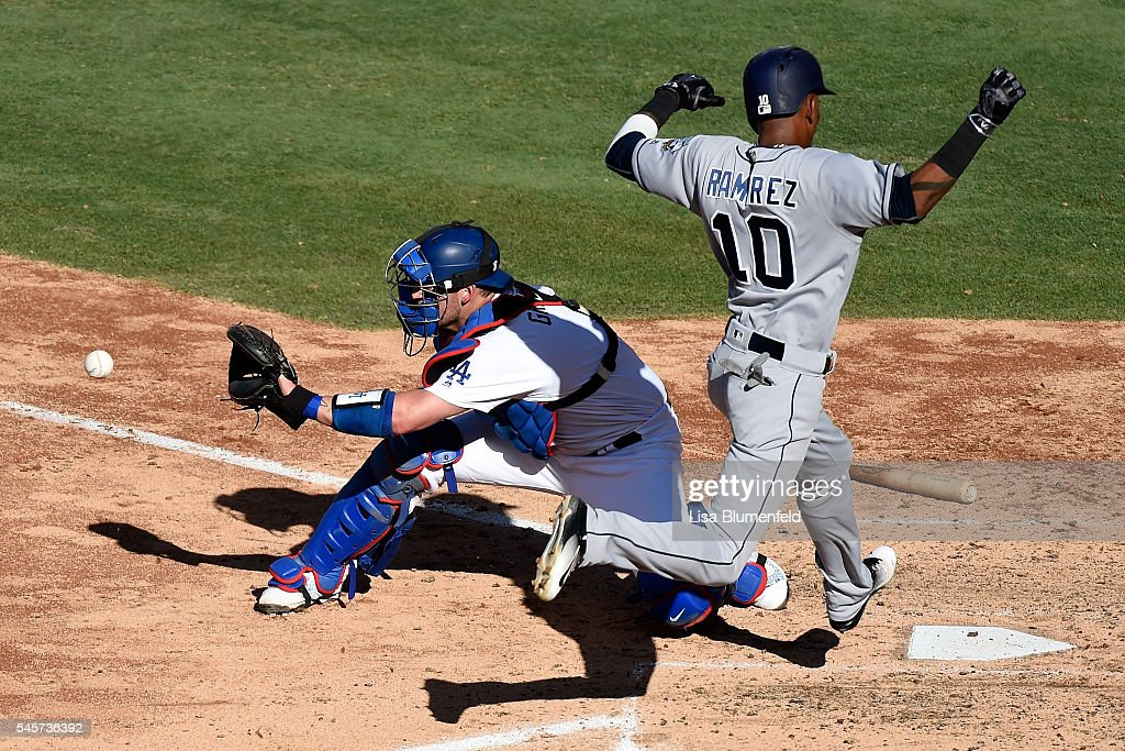 Alexei Ramirez #10 of the San Diego Padres scores in the fifth inning against Yasmani Grandal #9 of the Los Angeles Dodgers at Dodger Stadium on July 9, 2016 in Los Angeles, California.