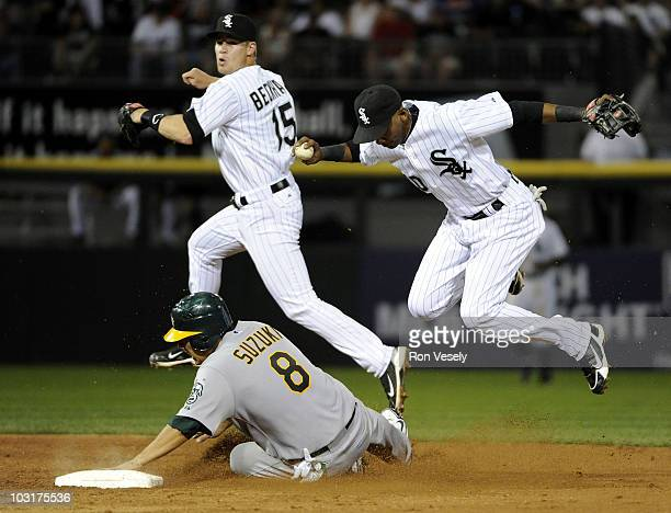 Alexei Ramirez records the out at second base after taking the throw from Gordon Beckham of the Chicago White Sox as Kurt Suzuki of the Oakland...