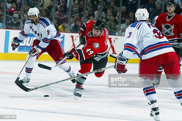 Alexei Zhitnik of the Buffalo Sabres takes a shot between Sandy McCarthy and Tom Poti of the New York Rangers during the NHL game between the New...