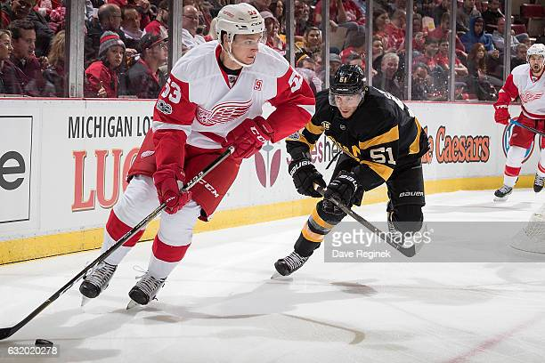 Alexey Marchenko of the Detroit Red Wings skates with the puck followed by Ryan Spooner of the Boston Bruins during an NHL game at Joe Louis Arena on...
