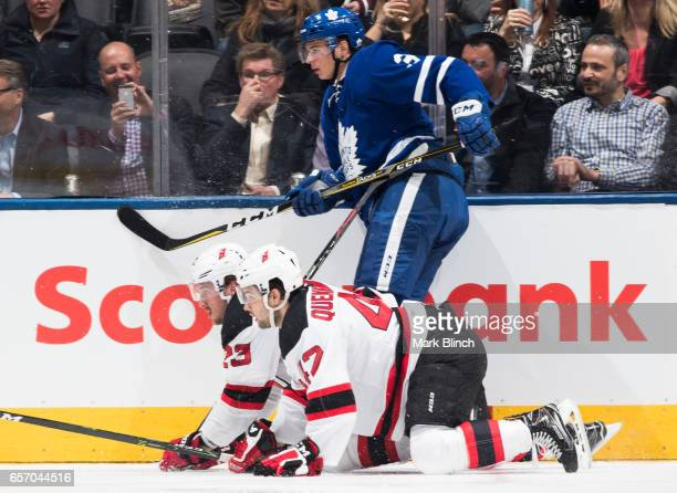 Alexey Marchenko of the Toronto Maple Leafs follows the play as Stefan Noesen and John Quenneville of the New Jersey Devils get up off the ice during...