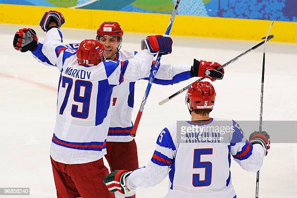 Alexey Morozov of Russia celebrates his secondperiod goal with teammates Andrey Markov and Ilya Nikulin during the ice hockey men's preliminary game...