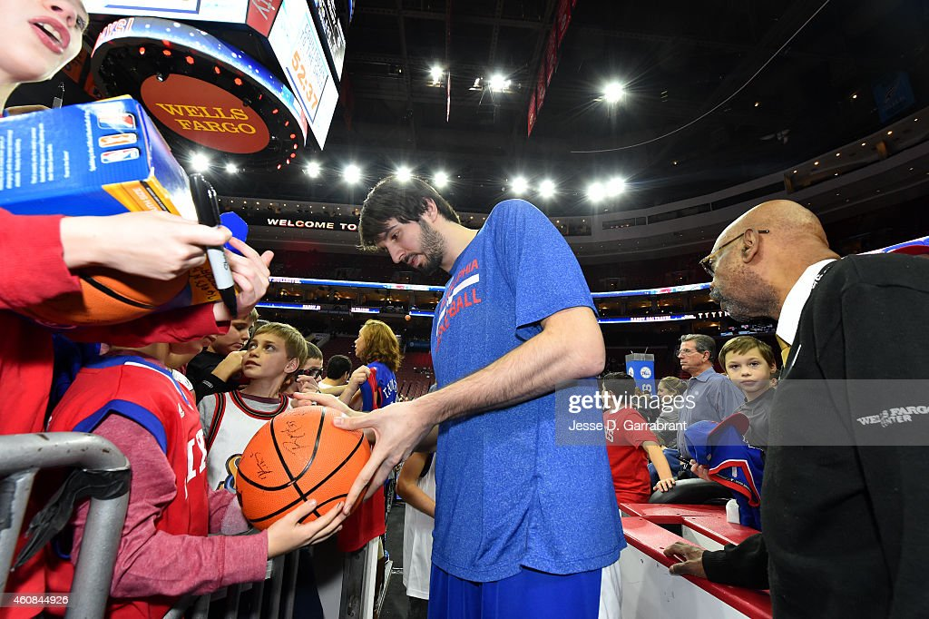 Alexey Shved #88 of the Philadelphia 76ers signs autographs before a game against the Charlotte Hornets on December 19, 2014 at Wells Fargo Center in Philadelphia, PA.