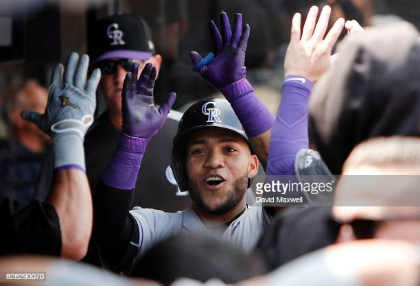 Alexi Amarista of the Colorado Rockies celebrates in the dugout after hitting a home run against the Cleveland Indians in the third inning at...