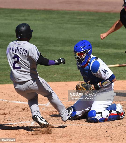 Alexi Amarista of the Colorado Rockies is tagged out at the plate by Yasmani Grandal of the Los Angeles Dodgers in the game at Dodger Stadium on June...