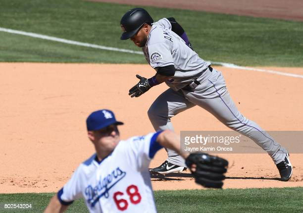 Alexi Amarista of the Colorado Rockies runs to second Ross Stripling of the Los Angeles Dodgers throws to the plate during the game at Dodger Stadium...