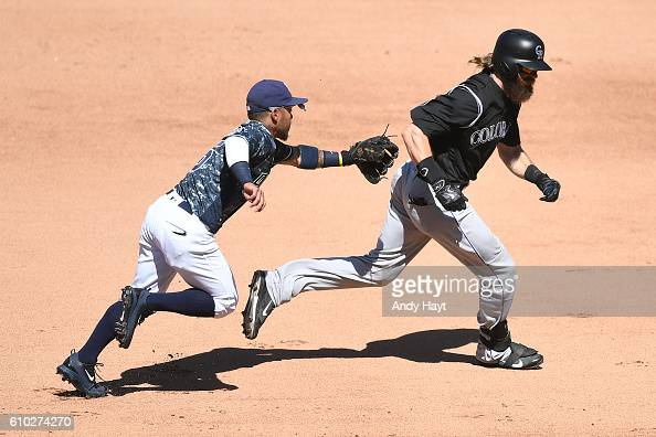 Alexi Amarista of the San Diego Padres catches Charlie Blackmon of the Colorado Rockies in a rundown between second and first base during the game at...