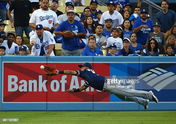 Alexi Amarista of the San Diego Padres dives to catch a fly ball to left field in first inning against the Los Angeles Dodgers during the MLB game at...