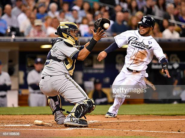 Alexi Amarista of the San Diego Padres is tagged out at the plate by Martin Maldonado of the Milwaukee Brewers during the second inning of a baseball...