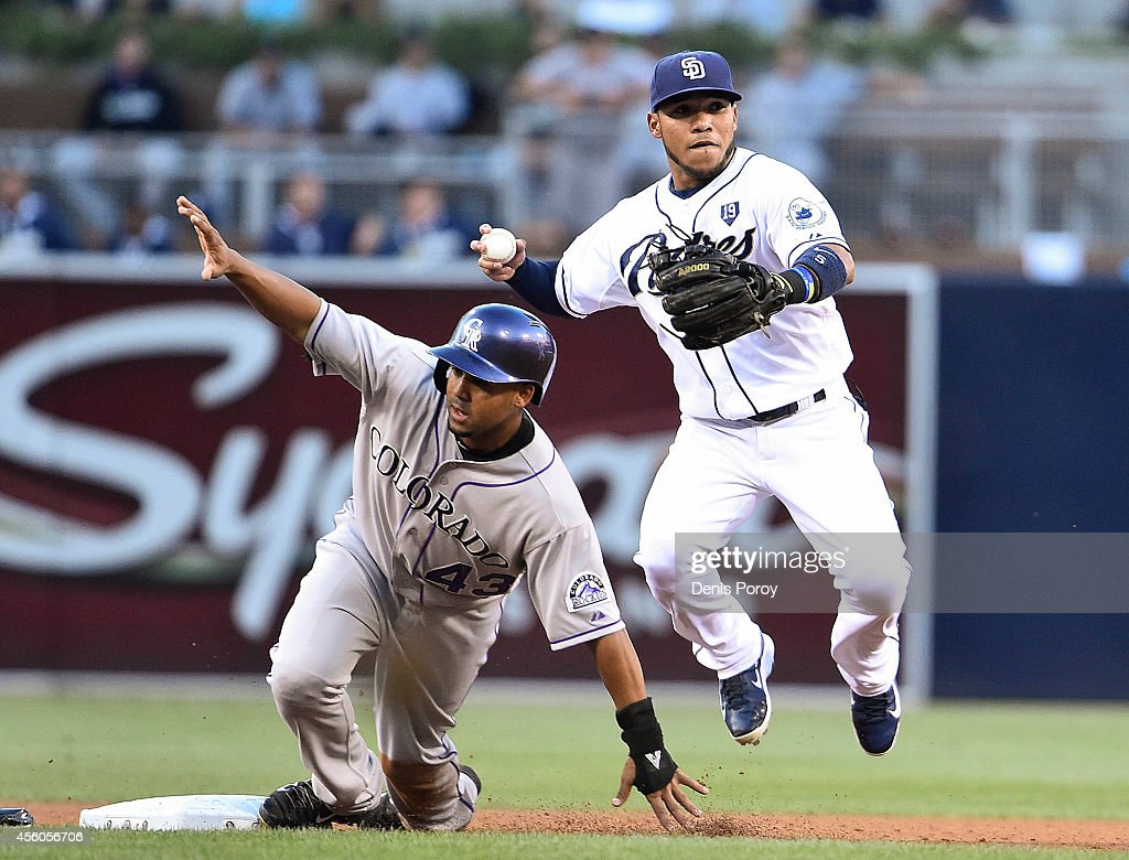 Alexi Amarista of the San Diego Padres jumps next to Rafael Ynoa of the Colorado Rockies as he turns a double play during the first inning of a...