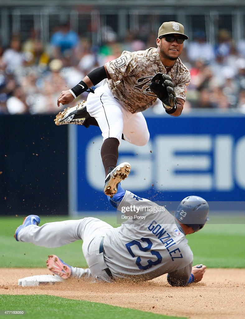 Alexi Amarista of the San Diego Padres jumps over Adrian Gonzalez of the Los Angeles Dodgers as he turns a double play during the fourth inning of a...