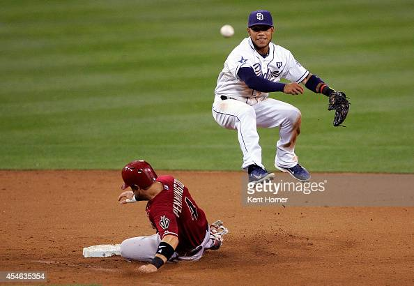 Alexi Amarista of the San Diego Padres leaps into the air over Cliff Pennington of the Arizona Diamondbacks while throwing to first base for the...