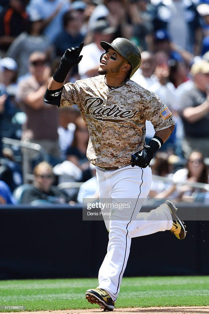 Alexi Amarista of the San Diego Padres points skyward after hitting a solo home run during the third inning of a baseball game against the Los...