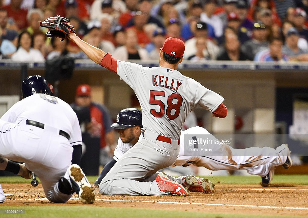 Alexi Amarista #5 of the San Diego Padres scores ahead of the throw to Joe Kelly #58 of the St. Louis Cardinals during the third inning of a baseball game at Petco Park July 30, 2014 in San Diego, California. Amarista scored on a wild pitch.