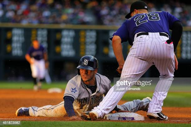 Alexi Amarista of the San Diego Padres slides safely into third base for a stolen base ahead of the tag by Nolan Arenado of the Colorado Rockies...