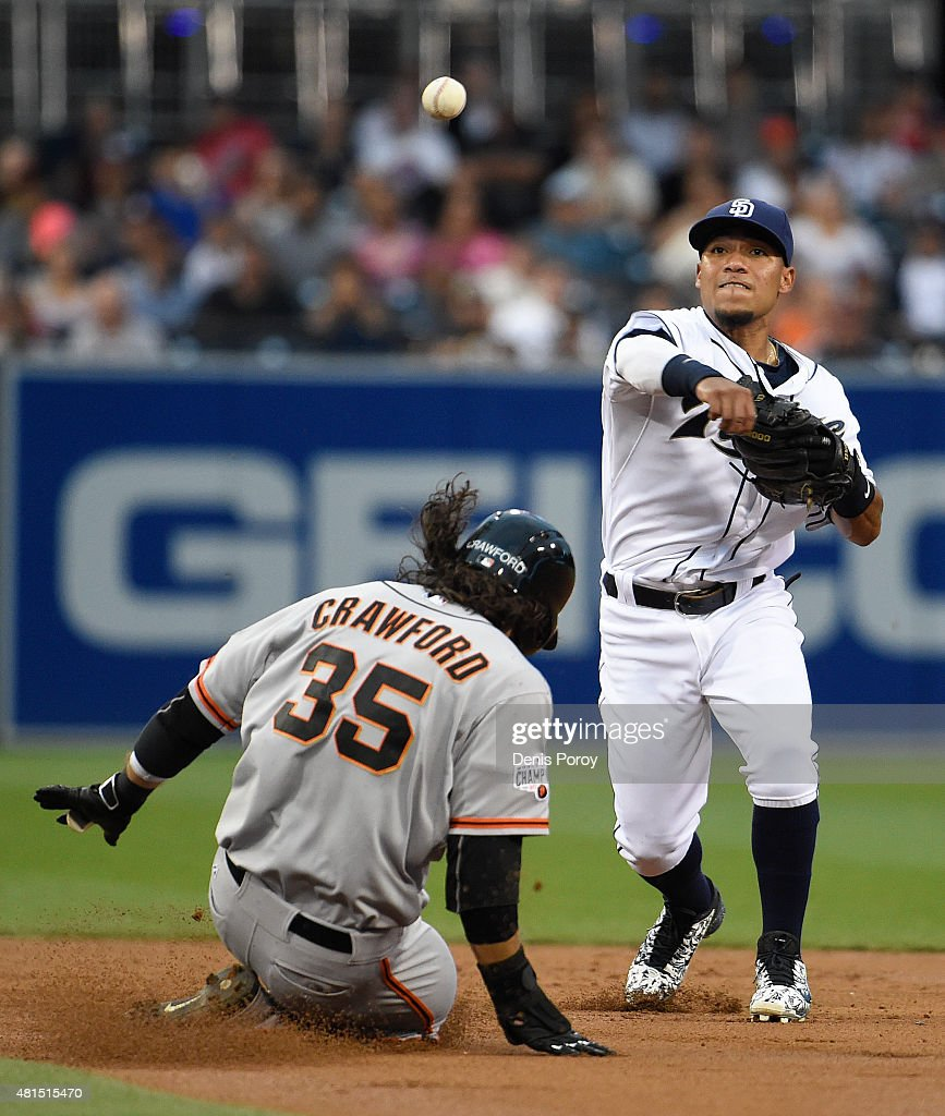 Alexi Amarista of the San Diego Padres throws over Brandon Crawford of the San Francisco Giants as he turns a double play during the second inning of...