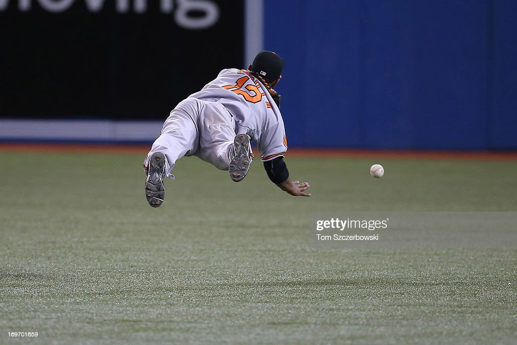Alexi Casilla of the Baltimore Orioles dives but cannot get to a bloop single in the eighth inning during MLB game action against the Toronto Blue...