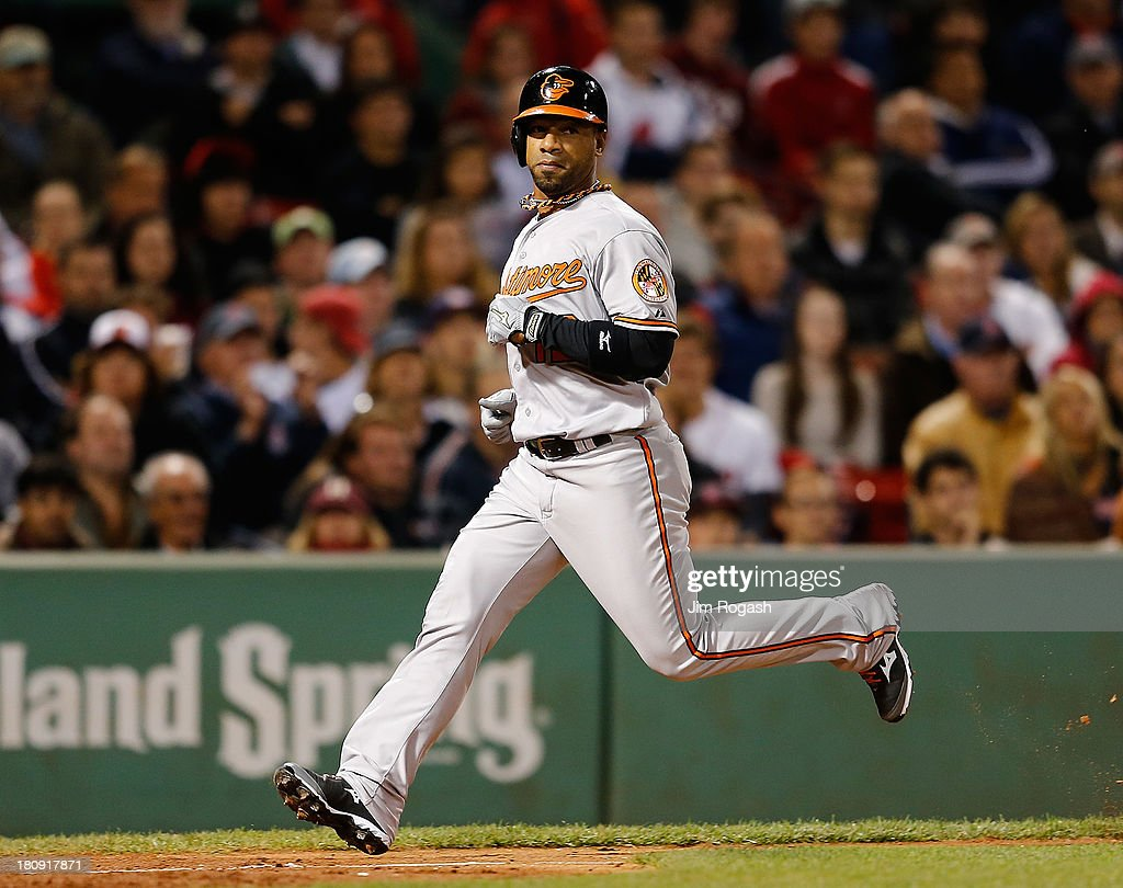 Alexi Casilla #12 of the Baltimore Orioles, pinch running for Danny Valencia, scores the winning run on a sacrifice fly, which was hit on a pitch thrown by Koji Uehara #19 of the Boston Red Sox, in the 9th inning at Fenway Park on September 17 in Boston, Massachusetts.