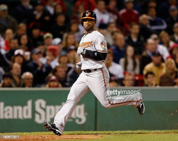 Alexi Casilla of the Baltimore Orioles pinch running for Danny Valencia scores the winning run on a sacrifice fly which was hit on a pitch thrown by...