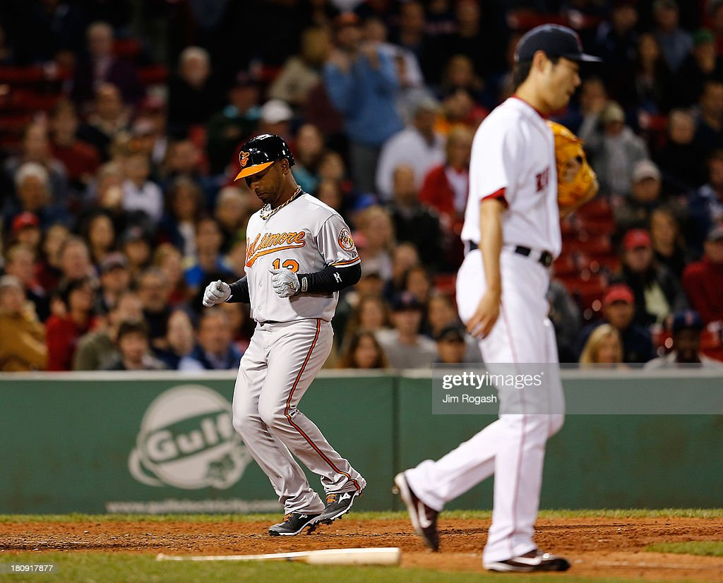Alexi Casilla #12 of the Baltimore Orioles, pinch running for Danny Valencia, scores the winning run on a sacrifice fly as Koji Uehara #19 of the Boston Red Sox walks back to the mound in the 9th inning at Fenway Park on September 17 in Boston, Massachusetts.