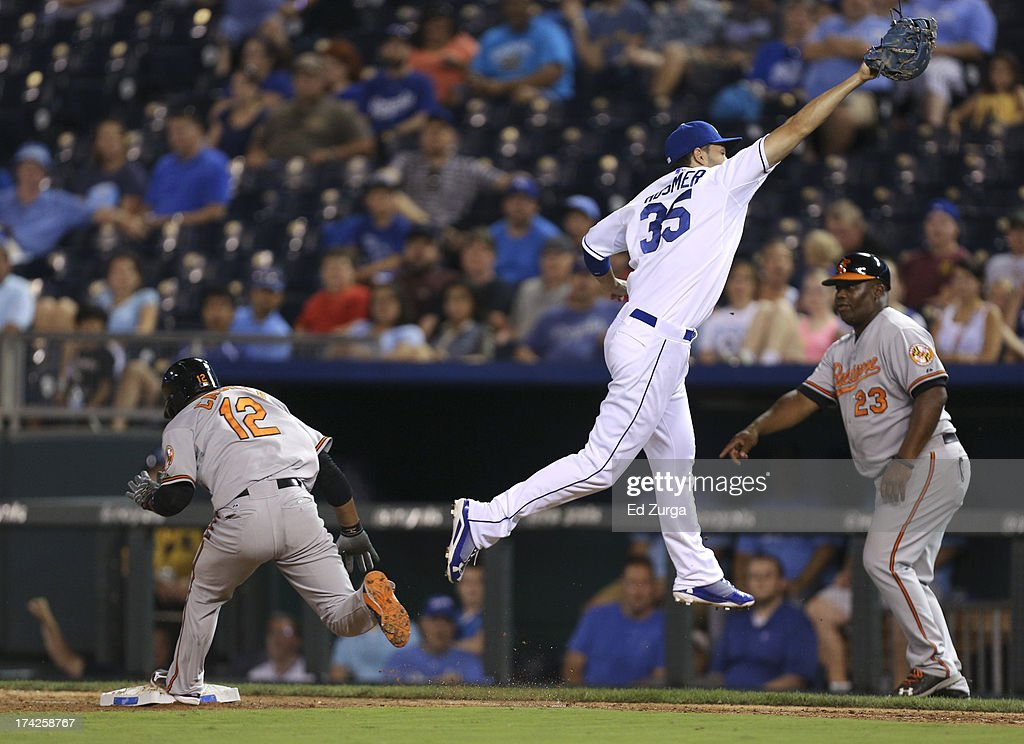 Alexi Casilla #12 of the Baltimore Orioles reaches first for a single as Eric Hosmer #35 of the Kansas City Royals leaps to catch the throw in the ninth inning at Kauffman Stadium on July 22, 2013 in Kansas City, Missouri.