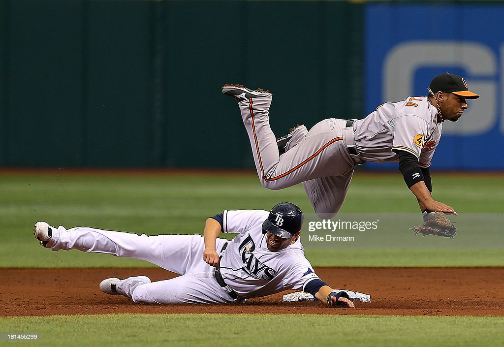 Alexi Casilla of the Baltimore Orioles turns a double play as David DeJesus of the Tampa Bay Rays slides into second during a game at Tropicana Field...