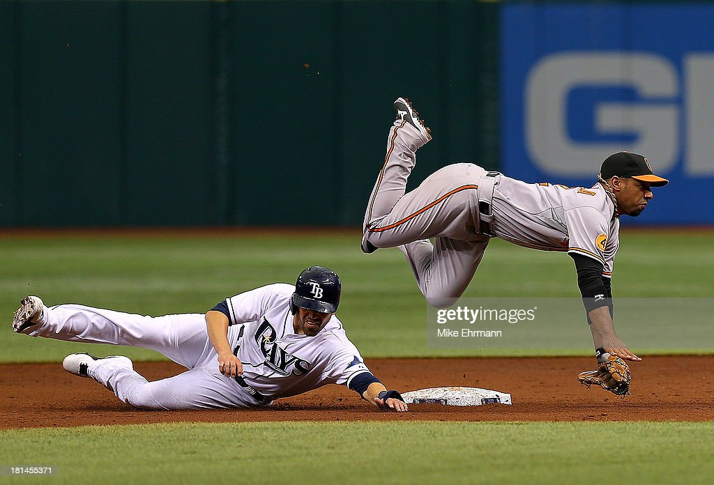 Alexi Casilla #12 of the Baltimore Orioles turns a double play as David DeJesus #7 of the Tampa Bay Rays slides into second during a game at Tropicana Field on September 21, 2013 in St Petersburg, Florida.