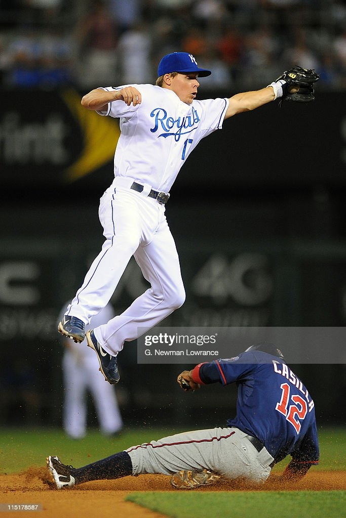 Alexi Casilla of the Minnesota Twins slides in with a stolen base as Chris Getz of the Kansas City Royals leaps up to catch the throw at Kauffman...