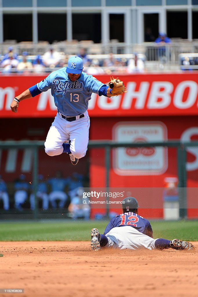 Alexi Casilla of the Minnesota Twins slides in with a stolen base as Mike Aviles of the Kansas City Royals leaps up to catch the throw at Kauffman...