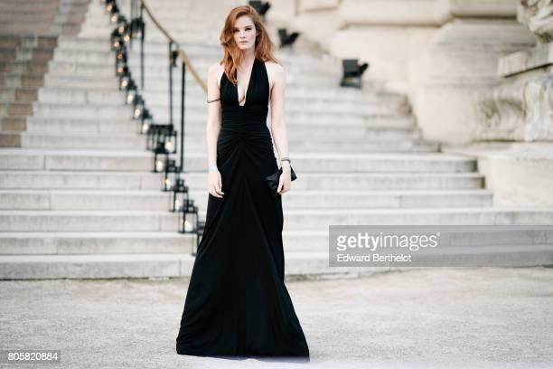 Alexina Graham wears a black dress and a black clutch outside the amfAR dinner at Petit Palais during Paris Fashion Week Haute Couture Fall/Winter...