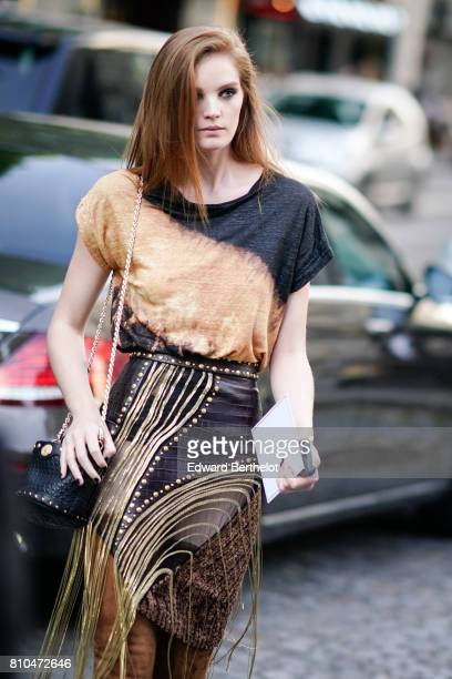 Alexina Graham wears a brown and black tshirt a black leather skirt with golden fringes a black bag and thigh high denim brown boots outside the...