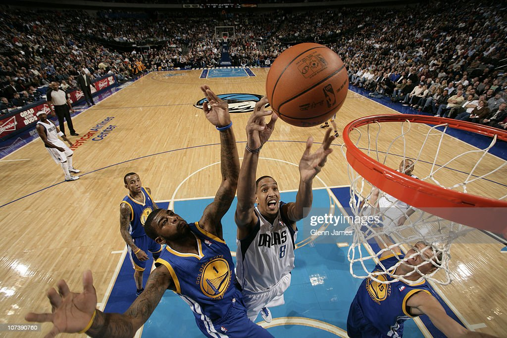Alexis Ajinca #8 of the Dallas Mavericks goes up for a rebound against Dorrell Wright #1 and Andris Biedrins #15 of the Golden State Warriors during a game on December 7, 2010 at the American Airlines Center in Dallas, Texas.