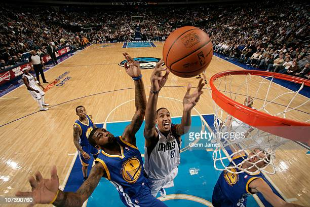 Alexis Ajinca of the Dallas Mavericks goes up for a rebound against Dorrell Wright and Andris Biedrins of the Golden State Warriors during a game on...
