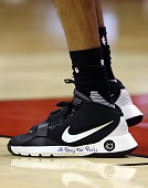 Alexis Ajinca of the New Orleans Pelicans has #PrayForParis written on his shoe during an NBA game against the Toronto Raptors at the Air Canada...