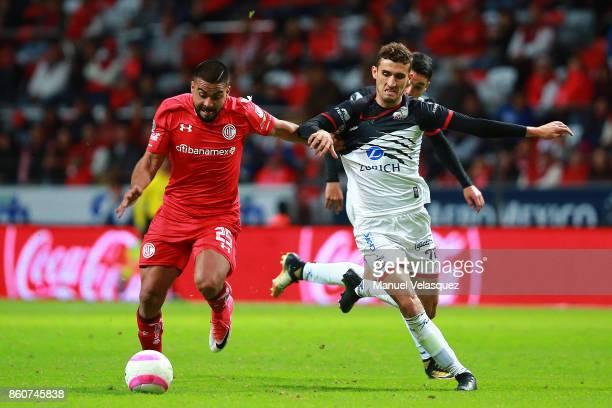 Alexis Canelo of Toluca struggles for the ball with Rodrigo Godinez of Lobos BUAP during the 13th round match between Toluca and Lobos BUAP as part...